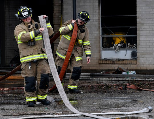 Abilene firefighters clean up after fighting an early-morning blaze at the Maison Blanche apartments Wednesday.