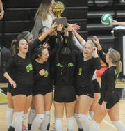 The Dublin volleyball team lifts its bi-district playoff trophy after sweeping Coahoma on Tuesday at Abilene High School.