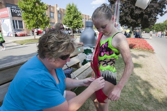 Mindy Bolinger (left), pins a sash to her daughter, Brianna Bolinger, 11, a few minutes before Brianna is due to twirl her baton in the evening's Main Street Parade, with three other winners of an earlier twirling contest at the Indiana State Fair, Indianapolis, IN, Friday, August 14, 2009.