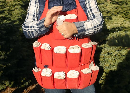 Karen Billick wears an apron with varying price tags in each pocket as she and husband Randy tag trees for harvest at their Huberts Christmas Trees in Bremerton in November.
