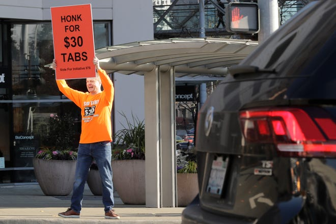 Anti-tax activist Tim Eyman holds a sign supporting Initiative 976, which would cut most car registration tabs to $30 in Washington state, Tuesday, Nov. 5, 2019, on election day in Bellevue, Wash. If passed by voters, the measure would leave state and local governments scrambling to pay for road paving and other transportation projects. (AP Photo/Ted S. Warren)
