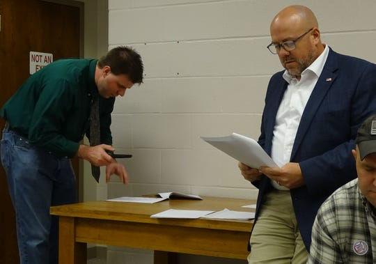 Kevin Myers, right, who won reelection as an at-large member of Bucyrus City Council, checks out newly posted election results Tuesday night at the Crawford County Board of Elections. At left is attorney Michael Bear, county chairman of the Republican party.