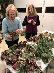 The evening before The Earth, Wind and Flowers Garden Club decorated the Bucyrus Historical Society, Dianna Zaebst and June Rauchenstein assembled 13 units for the staircase railing.