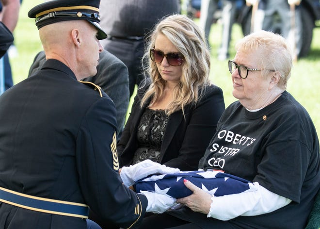 A burial flag is given to Korean War veteran Robert Bray's sister Cleo Jones during an official ceremony at Bainbridge cemetery. Bray, a Korean War veteran, was laid to rest in Bainbridge after being declared deceased in 1953 by the Army on Nov. 6, 2019.