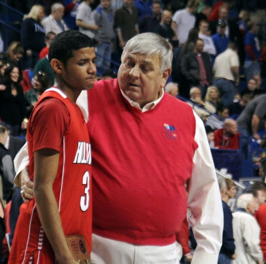 Holmes athletic director Stan Steidel comforts Holmes graduate and current University of Alabama basketball player James Bolden at midcourt after Holmes lost 65-61 to Madison Central in overtime in the KHSAA Sweet 16 quarterfinals March 8, 2013 at Rupp Arena in Lexington.