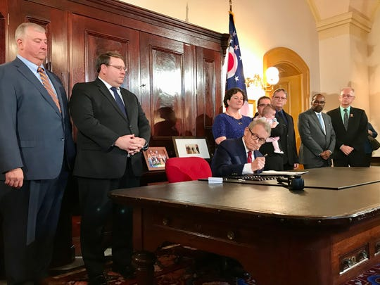 "Ohio Gov. Mike DeWine signs ""Tyler's Law"" on Wednesday, Nov. 6, 2019. The bill makes several changes to amusement ride safety. Amber Duffield, whose son Tyler Jarrell was killed while on an amusement ride in 2017, stood behind DeWine as he signed the bill."