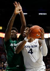 Xavier Musketeers forward Tyrique Jones (4) drives against Jacksonville Dolphins forward Bryce Workman (13) in the first half of NCAA basketball game between the Xavier Musketeers and the Jacksonville Dolphins at the Cintas Center in Cincinnati on Tuesday, Nov. 5, 2019.