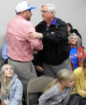 New Mayor Mark Mills is congratulated by outgoing Mayor Steve Mercer Tuesday at the Coshocton Count Board of Elections. Mills had 1,711 votes to Mercer's 1,072 votes in unofficial totals.