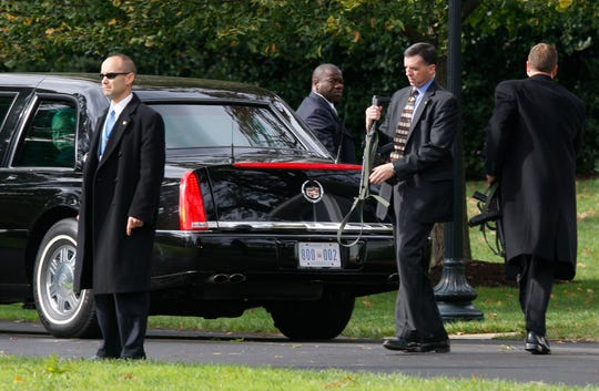 U.S. Secret Service agents get in position around the limousine carrying President George W. Bush, not pictured, during a security alert at the White House on Oct. 28, 2008. Seen through the limousine window at left is Barry Jackson, assistant to the President for Strategic Initiatives and External Affairs.