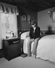 Vickie Raymond, UAW Local 1112, sitting on her mother Margie's bed in her bedroom, (24 years in at GM Lordstown Complex, trim and paint shop), East Rochester, OH, 2019.