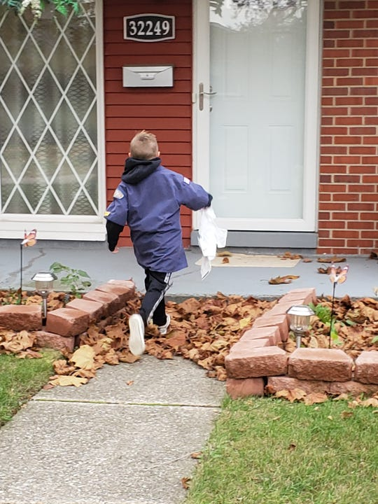 A Cub Scout from Pact 1478, St. Anne Catholic Church, Warren, Mich. delivers a food collection bag in Warren