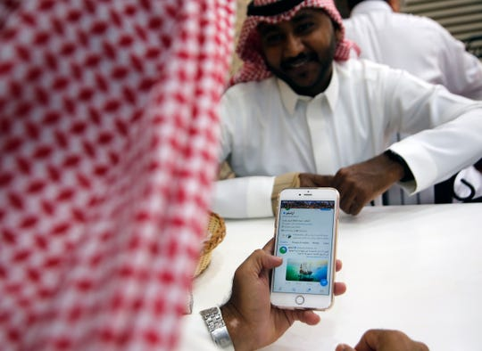 A man reads Aramco's twitter page at a coffee shop in Jiddah, Saudi Arabia, Sunday, Nov. 3, 2019.