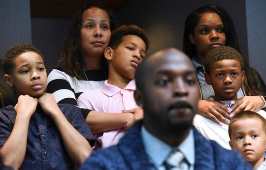 Marcus Riley of Bolingbrook, Ill., foreground, speaks during a press conference Tuesday, Nov. 5, 2019 in Aurora, Ill., about how he and other families, background, were asked to move because others didn't want to sit by them at a Naperville, Ill., Buffalo Wild Wings restaurant.