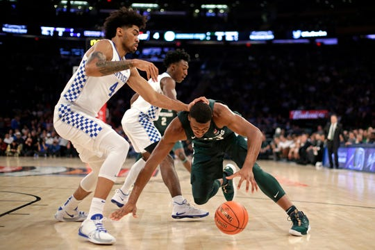 Michigan State forward Xavier Tillman falls to the court in front of Kentucky forward Nick Richards.