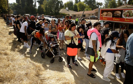 People line up around the block of singer Chris Brown's home in the Tarzana area of Los Angeles, Nov. 6, 2019.
