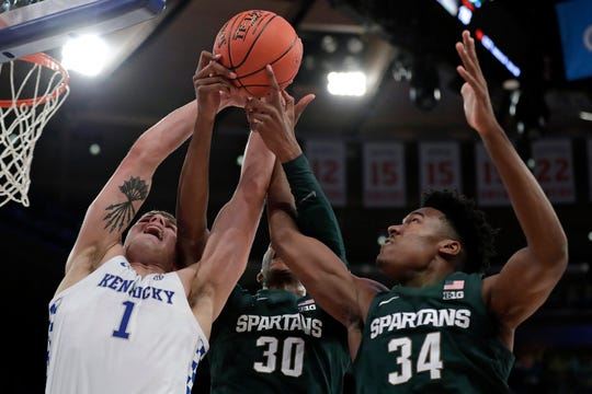 Kentucky forward Nate Sestina (1) vies for a rebound with Michigan State forwards Marcus Bingham Jr. (30) and Julius Marble (34) during the first half.