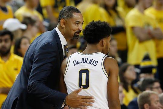 Michigan head coach Juwan Howard talks with guard David DeJulius.