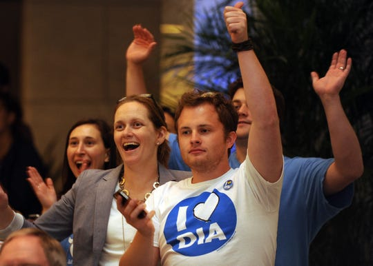 Campaign workers Dr. Kate Groninger, 2nd from left, and Brandon Hynes (Heart DIA tee) cheer as election results are read at the Detroit Institute of Arts on August 7, 2012.