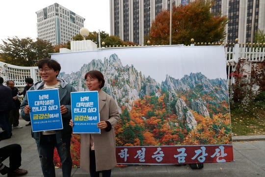 Protesters pose with an image of North Korea's Diamond Mountain during a rally calling for the resumption of Diamond Mountain tourism in Seoul, South Korea, Monday, Oct. 28, 2019.