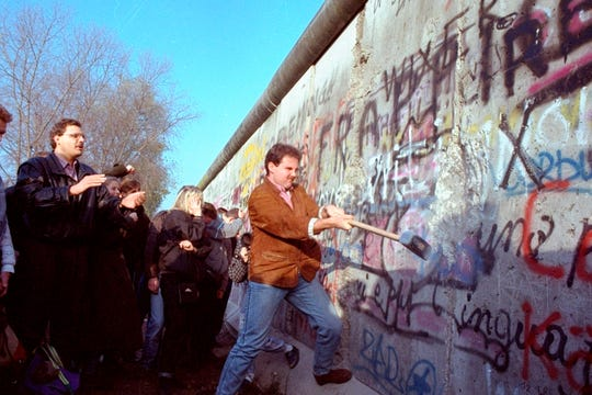 FILE - In this Sunday, Nov. 12, 1989 file photo, an unidentified West Berliner swings a sledgehammer, trying to destroy the Berlin Wall near Potsdamer Platz in Berlin, where a new passage was opened nearby.