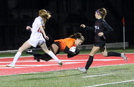Elmira goalie Delaney Malone dives after the ball as North Rockland's Kelly Brady and Elmira's Jodee White go by during a Class AA girls soccer regional game Nov. 5, 2019 at Waverly Memorial Stadium.