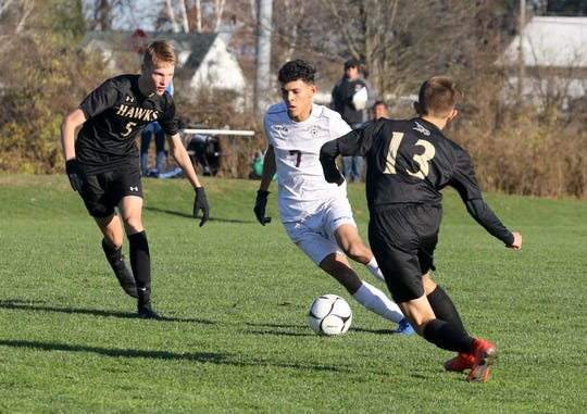 Ossining's Jose Padilla (7) tries to dribble between Corning players Micah Cornfield (5) and Luke Johns (13) during a Class AA boys soccer regional semifinal Nov. 6, 2019 at the Wright National Soccer Campus in Oneonta.