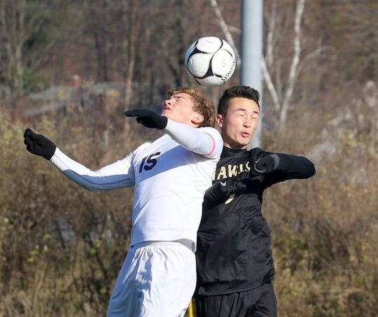 Ossining's Nolan Lenaghan (15) and Corning's Noah Hunkele go up for a ball during a Class AA boys soccer regional semifinal Nov. 6, 2019 at the Wright National Soccer Campus in Oneonta.