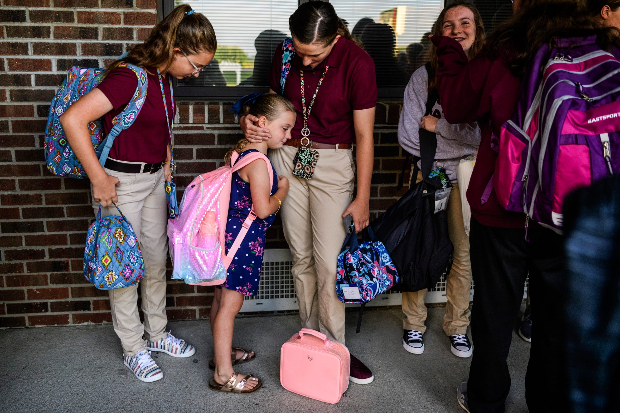 On the first day of school, Anna and Madelyn comfort Paige outside of Cairo Elementary School, where Paige attends, as they wait for a bus to take them to North Middle School Wednesday morning, Aug. 7, 2019. Paige, now a third-grader, shed a few tears when she realized she would be separated from her older sisters again after spending summer break constantly by their side.
