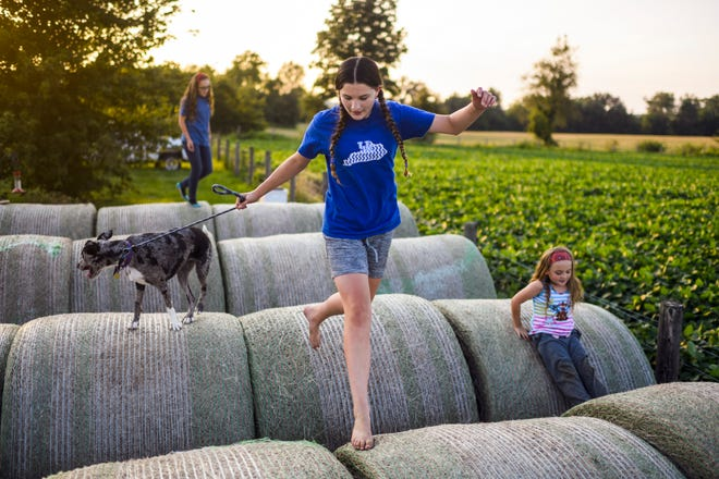 The sun sets at the Bennett homestead in Robards, Ky., as Madelyn, center, leads her dog Skye over hay bales while jumping around with her sisters Anna, left, and Paige on the evening of Anna's 12th birthday Thursday, July 25, 2019. The sisters spend the majority of their free time playing outside when the weather is nice.