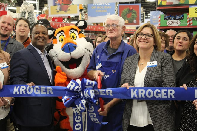 Ronald Valentine, center, cuts the ribbon to open Kroger's new Fremont store on Cedar Street Wednesday.