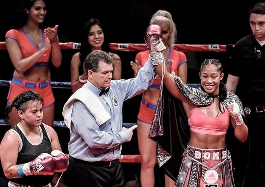 The referee lifts Alycia Baumgardner's arm in victory after the Fremont native's six-round bout against Annette Pabello.