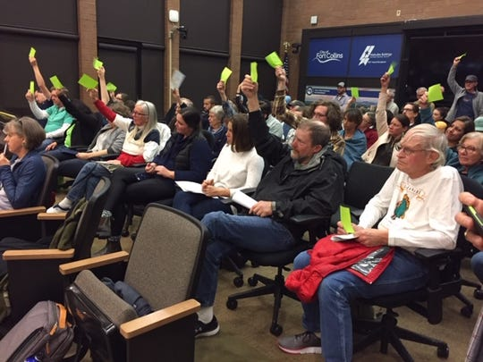 An overflow crowd at City Council waves green cards signaling support for lower density development at the former Hughes Stadium in west Fort Collins.