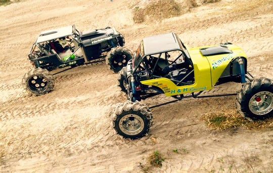 Chris Libak races an early version of his mega truck Animalistic (right) at Redneck Mud Park in Punta Gorda