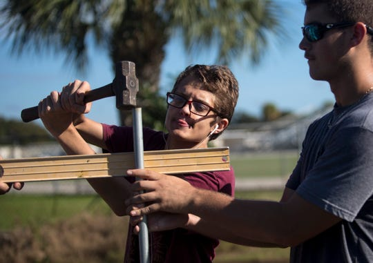 Riverdale High School students Colin Drury, left, and Wyatt Robinson work on installing the school's new hydroponic garden system on Tuesday, Nov. 5, 2019.