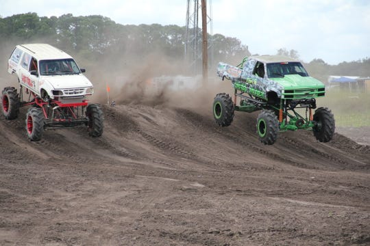 "The mega truck Grass Money wins by a hair against Last Call in a scene from the TV series ""Dirty Mudder Truckers."""