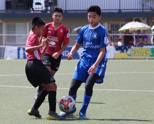 Wings FC's Paul Webb, left, and Guam Shipyard Wolverines' Landen Diaz battle for possession of the ball during a Week 5 Hurao Division match of the Aloha Maid Minetgot Cup Elite Youth League Saturday at the Guam Football Association National Training Center.