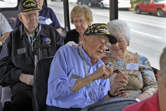 USS Indianapolis survivor Art Leenerman, center, chats with his wife Ethel, right, as they and other survivors and families wait to be taken from the Indianapolis War Memorial to the Columbia Club during the USS Indianapolis survivors' reunion weekend on Aug. 2, 2013.