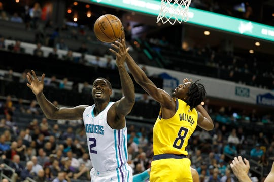 Charlotte Hornets' Marvin Williams (2) and Indiana Pacers' Justin Holiday (8) reach for a rebound during the first half of an NBA basketball game in Charlotte, N.C., Tuesday, Nov. 5, 2019.