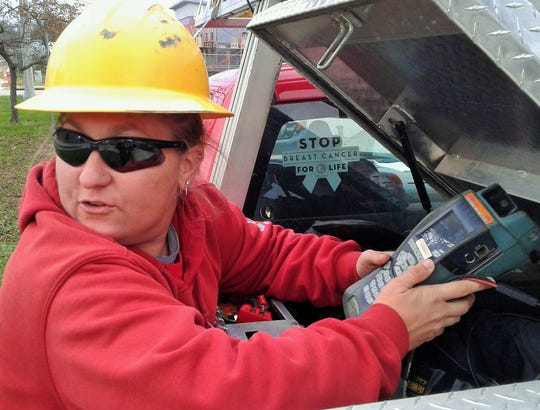 Wearing a yellow hard hat, Jessi Kettler retrieves a high-speed Internet testing meter from the tool box of her South Slope Cooperative truck. An installer/repair technician for 16 years, she thinks it's especially important to wear head protection where workers are digging with back hoes or other heavy equipment.