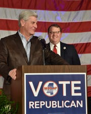 Mississippi Gov. Phil Bryant, flanked by state Republican Party Chairman Lucien Smith, addresses the crowd at an MSGOP election-night party on Tuesday, Nov. 5, 2019.