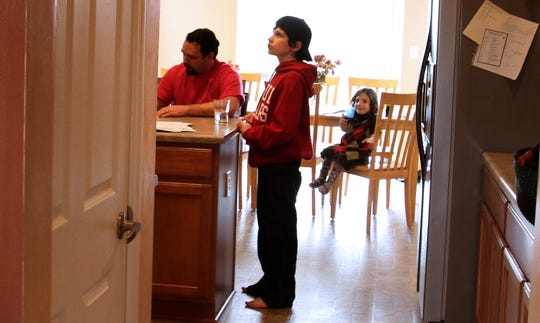 In this March 2011 file photo from the Indianapolis Star, Jake Barnett, 12, center, takes a break from studying for his college finals. In the background, Natalia Barnett sits on a kitchen chair, and Michael Barnett is seen at the kitchen island.