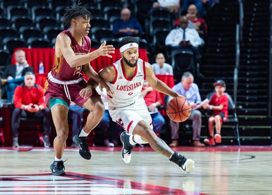 UL guard Trajan Wesley takes the ball upcourt in a season-opening win over Loyola of New Orleans on Tuesday night. Wesley reinjured a foot in the victory.