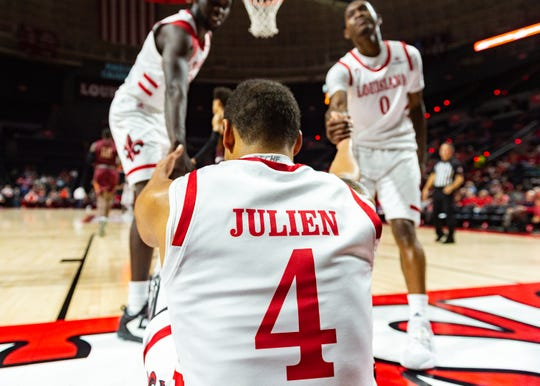 Teammates Dou Gueye (left) and Cedric Russell (right) help Kobe Julien up during UL's season-opening win over Loyola of New Orleans.