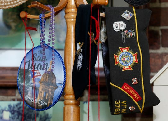 Bernard Paumier's VFW hat and tie hang from a coat rack in his home along with a painting of San Juan, Puerto Rico. Paumier learned to speak Spanish while in Puerto Rico with the Air Force. He's continued to use that skill to help people study for and pass U.S. citizenship tests.
