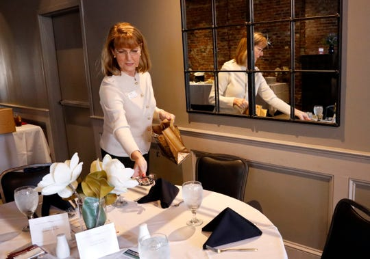 Margie Donnell places gifts onto a table as she and other Lancaster Fairfield County Chamber of Commerce employees prepare for a Chamber Cafe event Wednesday, Nov. 6, 2019, at Ale House 1890 in downtown Lancaster. Donnell has been the chamber's operations and marketing manager for three years.