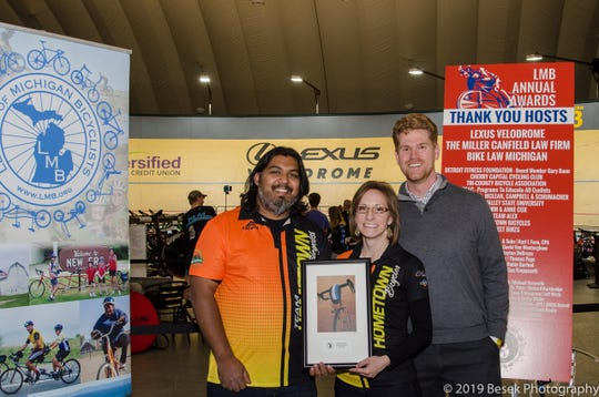 """Hometown Bicycles owners Shaun and Dawn Bhajan, seen with Michigan League of Bicyclists Executive Director John Lindenmayer, won Michigan's 2019 """"Shop of the Year"""" award that was presented at the Lexus Velodrome in Detroit, Oct. 19, 2019."""