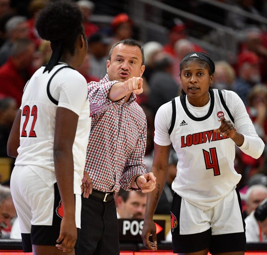 Louisville Cardinals head coach Jeff Walz talks with forward Elizabeth Dixon (22) and guard Elizabeth Balogun (4) during the second half at the KFC Yum! Center.  Louisville defeated Western Kentucky 75-56.  (Photo by Jamie Rhodes/