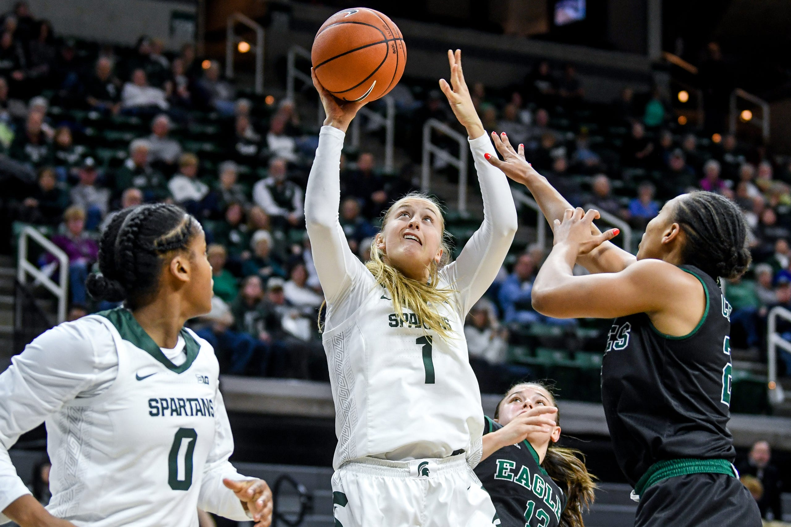 Michigan State's Tory Ozment, center, scores as Eastern Michigan's Corrione Cardwell defends during the  fourth quarter on Tuesday, Nov. 5, 2019, at the Breslin Center in East Lansing.