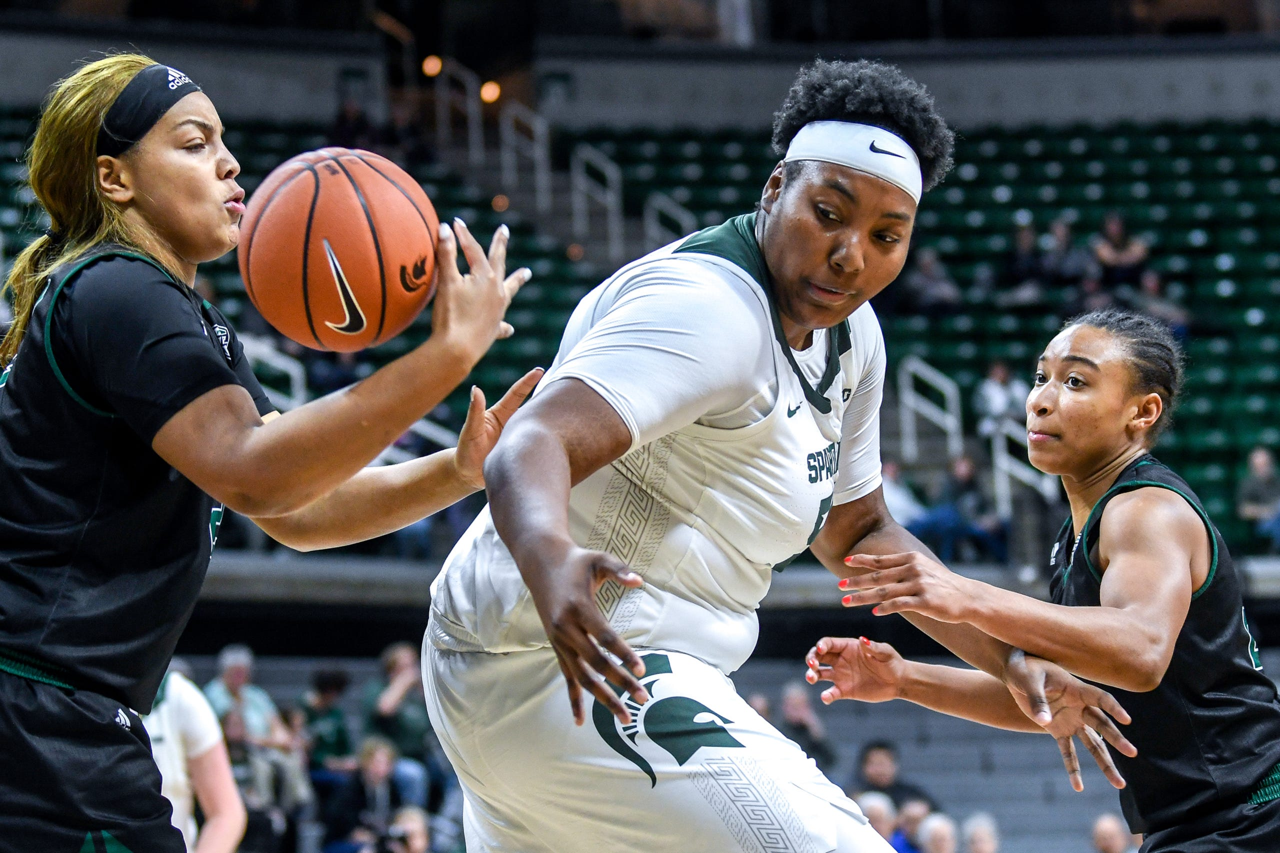 Michigan State's Cydni Dodd, center, goes for a rebound between Eastern Michigan's Laurel Jacqmain, left, and Constance Chaplin during the fourth quarter on Tuesday, Nov. 5, 2019, at the Breslin Center in East Lansing.