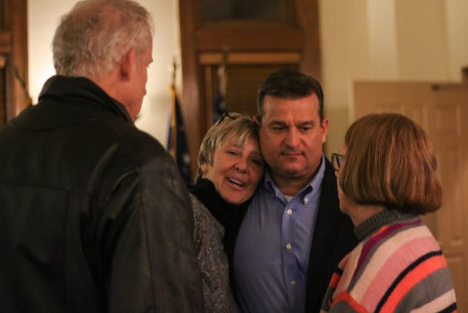Marion Mayor Scott Schertzer, center right, hugs City Auditor Kelly Carr, center left, who lost her bid for re-election Tuesday. Schertzer won a fourth term as the city's mayor.